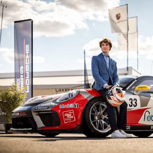 Evan Spenle standing by his Porsche race car
